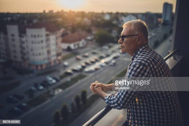 pensive senior man enjoying the view form his penthouse balcony at sunset. - introspection stock pictures, royalty-free photos & images