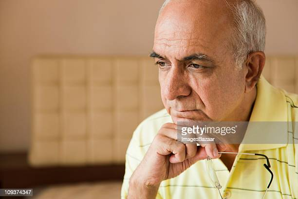 Pensive senior man, holding glasses indoors