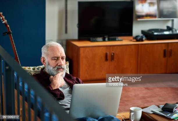 pensive senior man using laptop with hand on chin - solo 2018 film stock pictures, royalty-free photos & images
