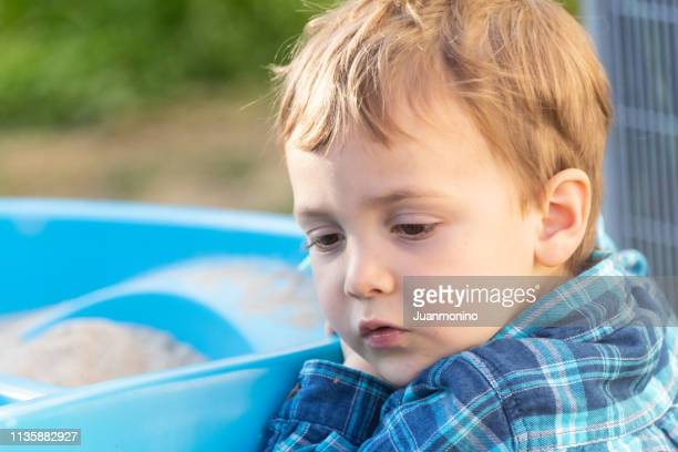 pensive serious three years old child looking down - shy stock pictures, royalty-free photos & images