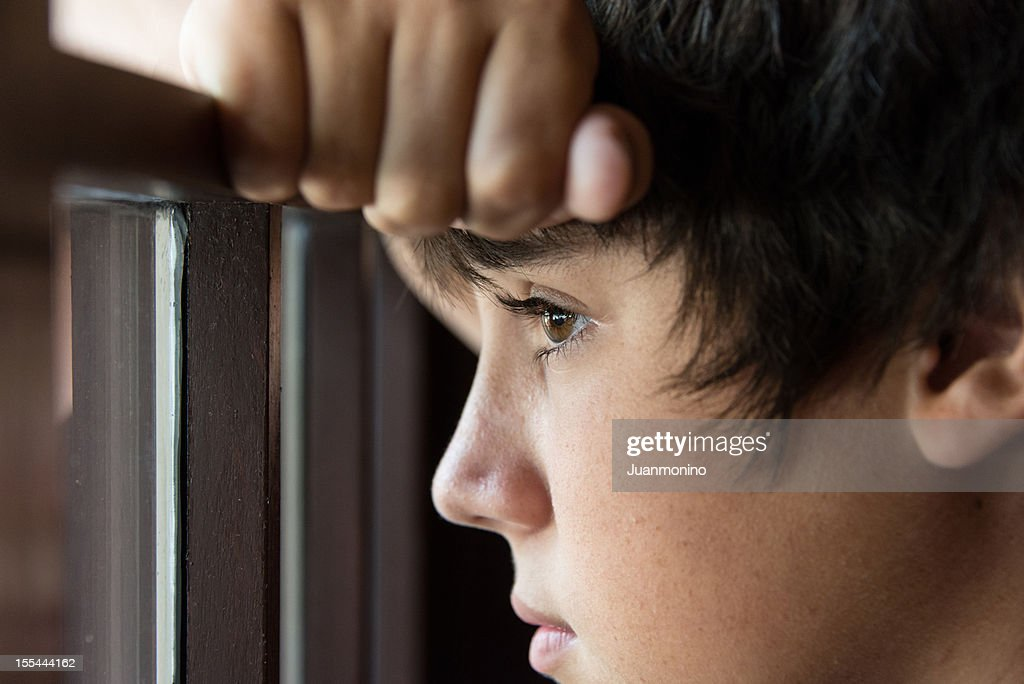 Pensive teenager looking through a window : Stockfoto