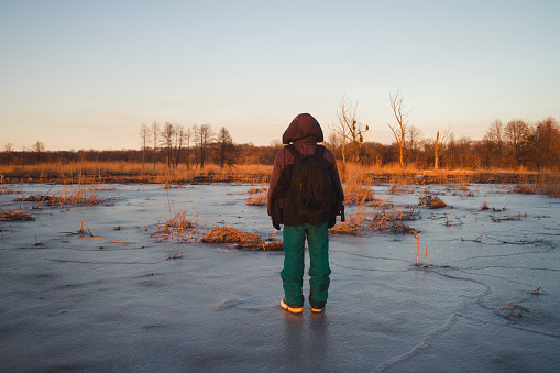 Pensive traveler standing on the ice 514062084