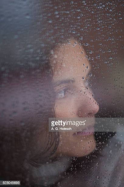 Pensive woman behind a window with rain drops