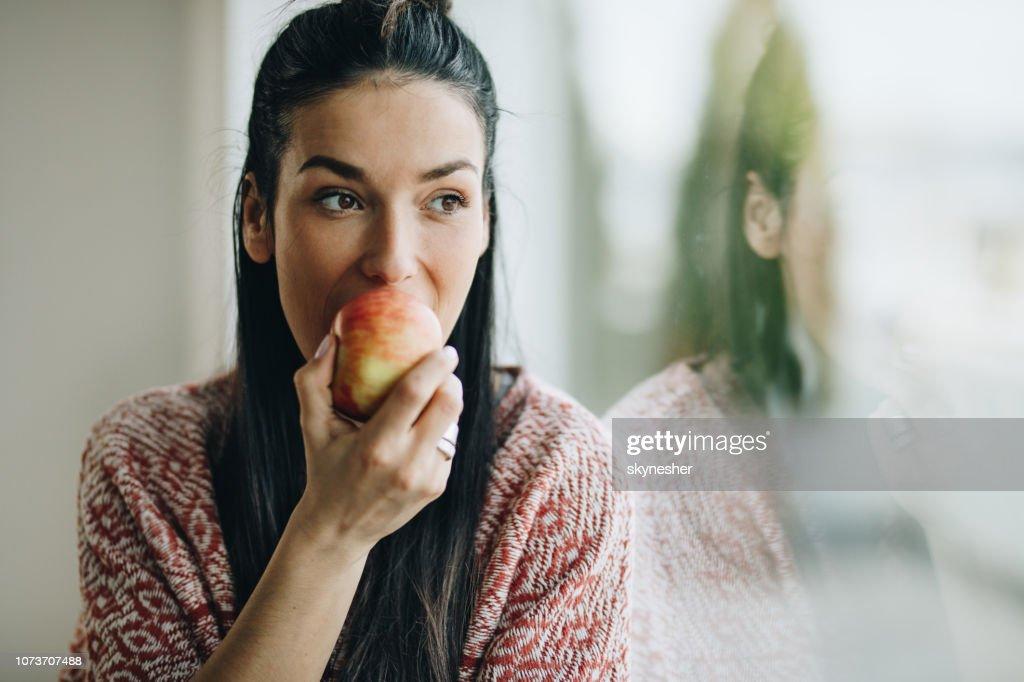 物思いにふける女性ウィンドウでリンゴを食べるします。 : ストックフォト