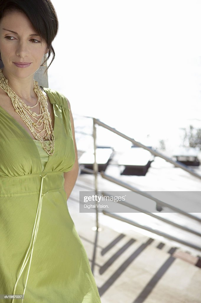 Pensive Woman in a Dress and Bead Necklace, Standing By Steps Outdoors : Stock Photo