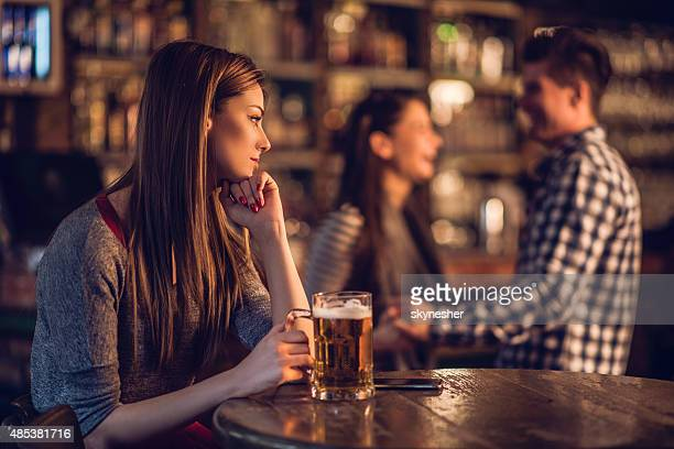 Pensive woman in bar looking at happy couple in background.