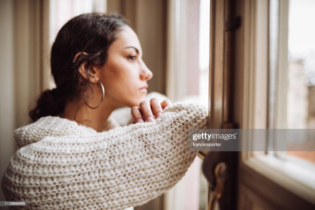 mujer pensativa frente a la ventana : Foto de stock