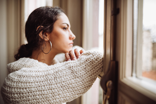 pensive woman in front of the window 1129696669