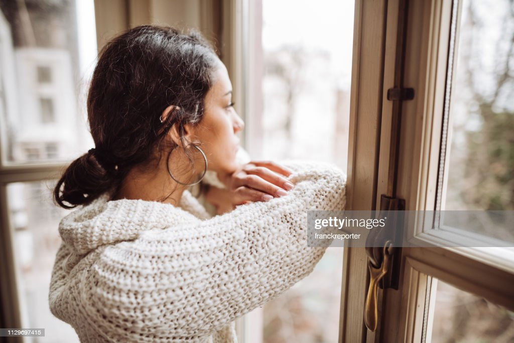 pensive woman in front of the window : Stock Photo