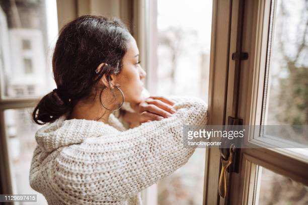pensive woman in front of the window - censura imagens e fotografias de stock