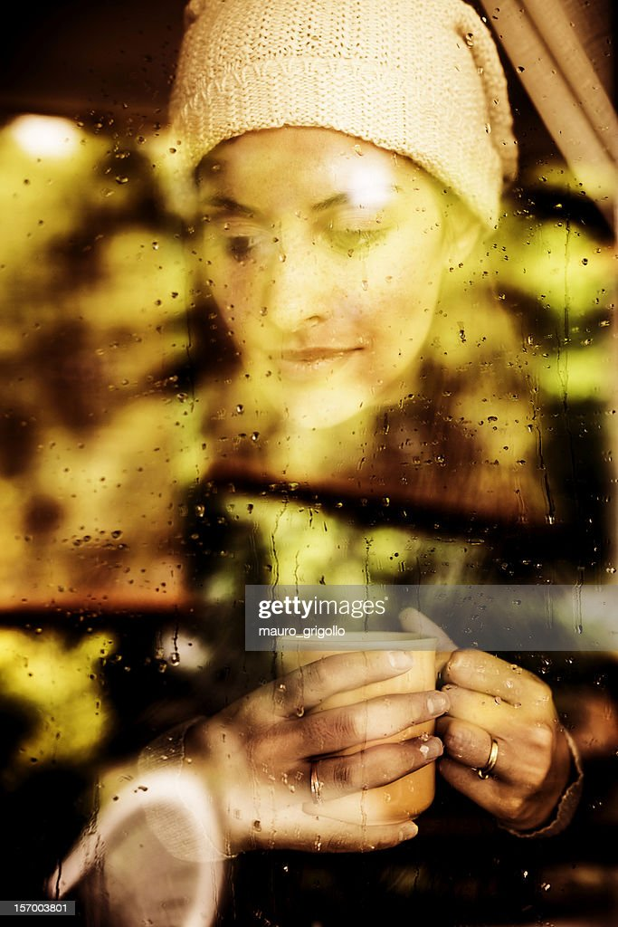 Pensive woman looking through a window : Stock Photo