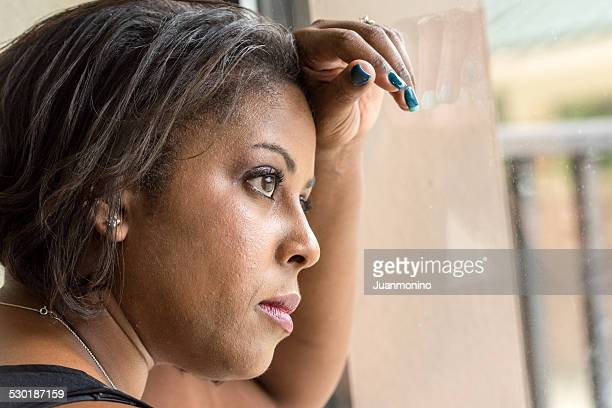 Pensive woman looking through the window