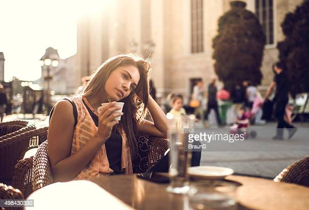Pensive woman relaxing in a city cafe and day dreaming.