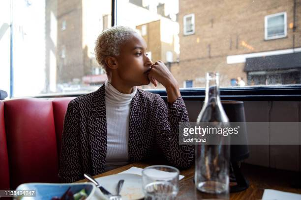 pensive woman sitting by herself in a restaurant at lunch break - introspection stock pictures, royalty-free photos & images