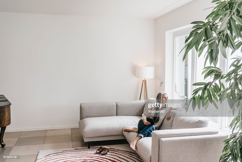 Pensive woman sitting with mini tablet on the couch looking through window : Stock Photo