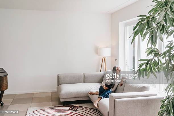 Pensive woman sitting with mini tablet on the couch looking through window