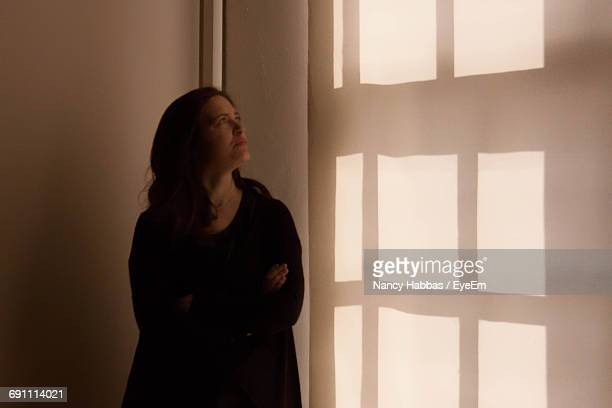 Pensive Woman Standing By Window At Home