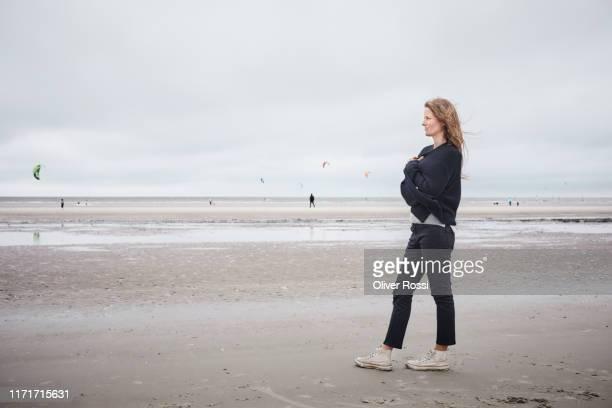 pensive woman standing on the beach - cardigan photos et images de collection