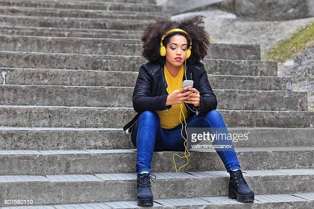 Pensive woman with yellow headphones listening music on stairs