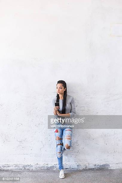 Pensive young asian woman leaning back on blank wall