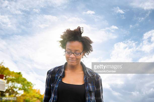 Pensive young black female walking and smiling looking down