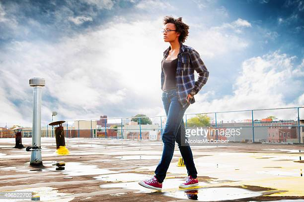 Pensive young black woman walking on wet rooftop profile