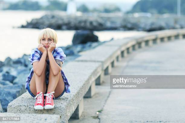 Mujer rubia joven pensativa sentado en la playa
