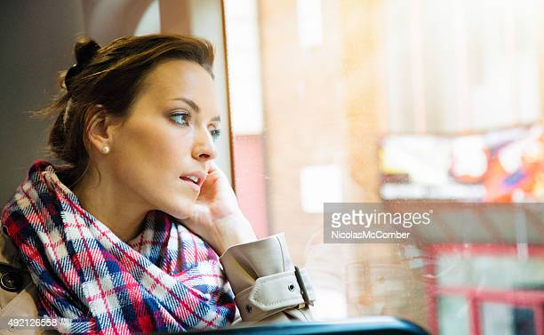 Pensive young British woman looking out of London bus window