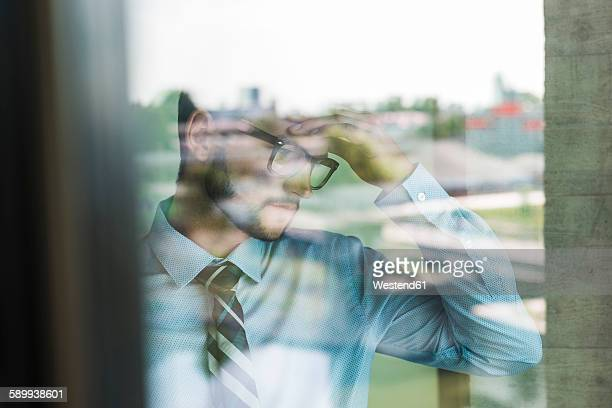 Pensive young businessman behind windowpane