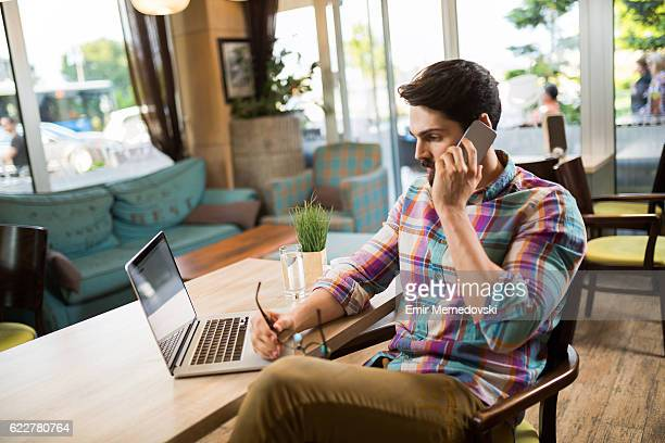Pensive young businessman talking on mobile phone in cafe.