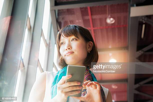 Pensive Young Japanese Woman daydreaming phone in hand