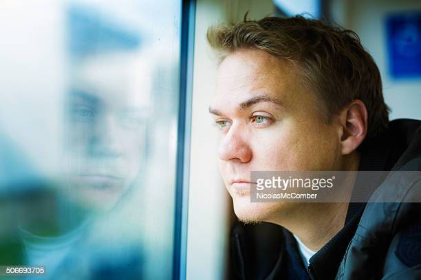 Pensive young man at window with reflection