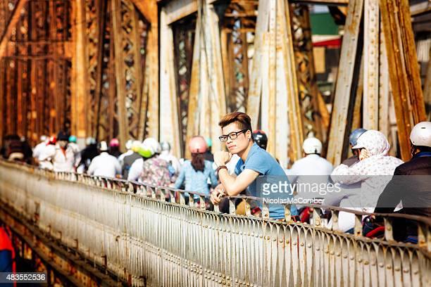 Pensive young man pauses Long Bien Bridge phone in hand