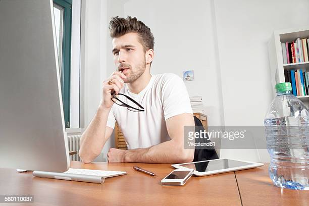 Pensive young man sitting at desk in an office
