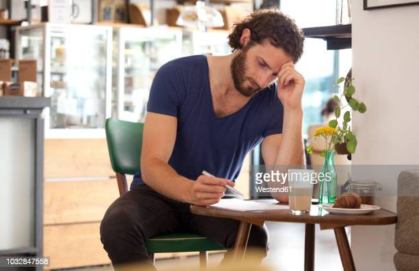 pensive young man sitting in a coffee shop writing letter - correspondence stock pictures, royalty-free photos & images