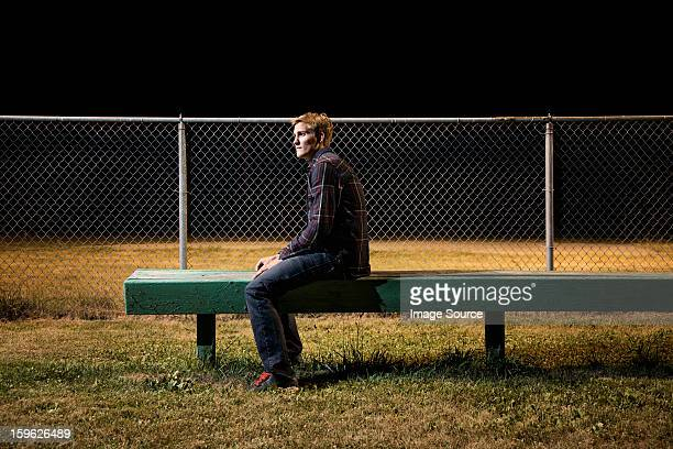 Pensive young man sitting on bleachers at night