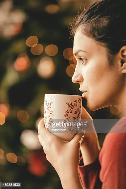 Pensive young woman drinking tea by the Christmas tree
