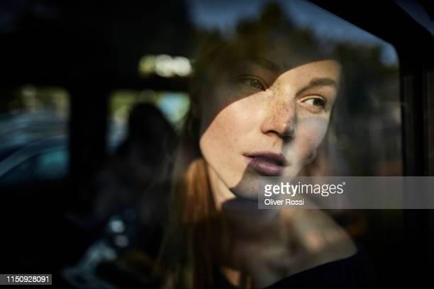 pensive young woman looking out of car window - rêvasser photos et images de collection