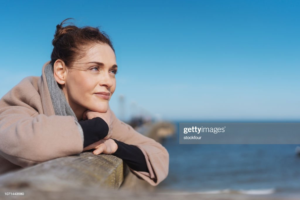 Pensive young woman relaxing on a wooden pier : Stock Photo