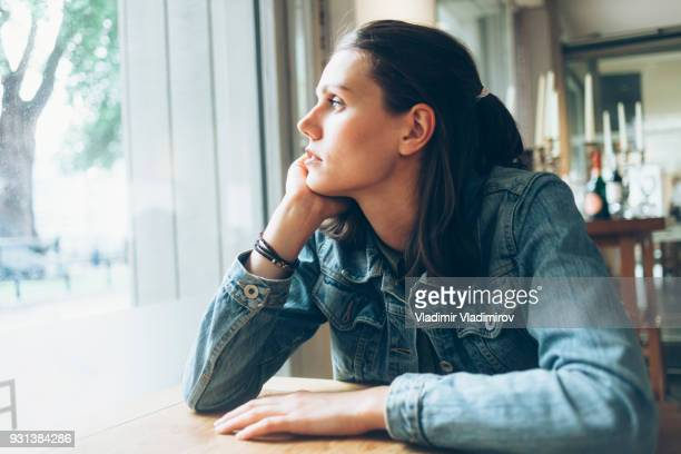 pensive young woman sitting in cafe alone - postpartum depression stock pictures, royalty-free photos & images