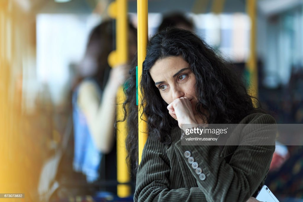 Pensive young woman traveling and holding smart phone : Stock Photo