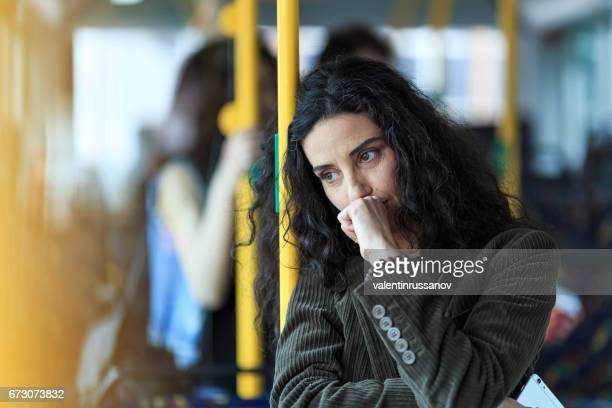 pensive young woman traveling and holding smart phone - underground stock photos and pictures