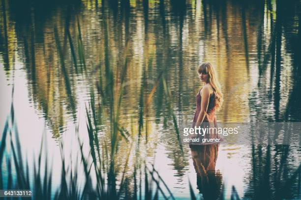 Pensive Young Woman Wading in Lake at Sunset
