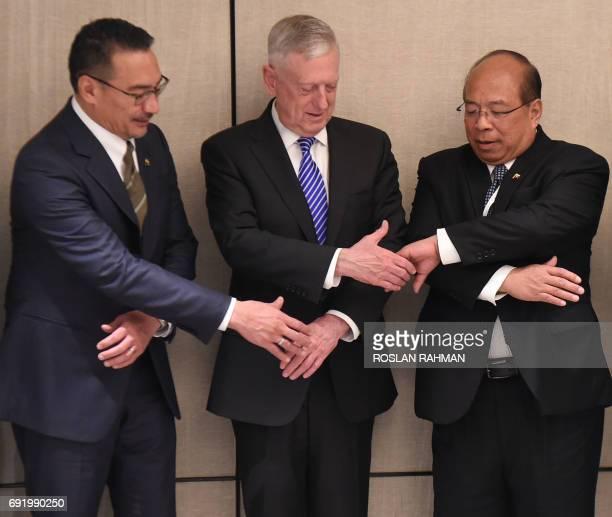 US Pentagon chief Jim Mattis reaches for hand shakes with Malaysian Defence Minister Hishammuddin Tun Hussein and U Thaung Tun National Security...