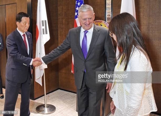 US Pentagon chief Jim Mattis shakes hands with South Korea's Defense Minister Han MinKoo while talking to Japan's Defence Minister Tomomi Inada...