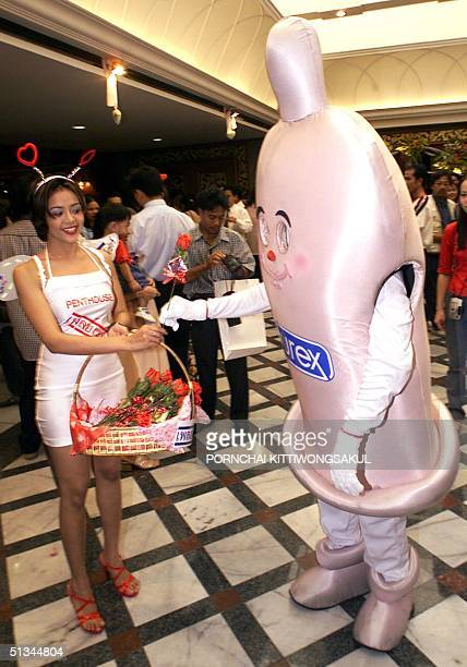 Penthouse magazine model and a man in a giant condom costume exchange a red rose on which is attached a condom 14 February 2000 during a promotional...