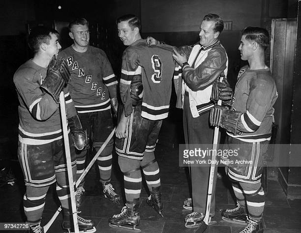 Pentti Lund who now wears No 9 gets measured for size by New York Rangers' coach Lynn Patrick who used to wear the No 9 jersey Looking on in the...