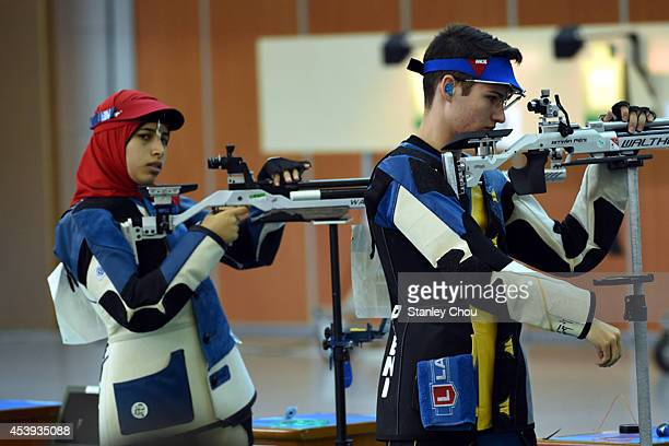 Peny Istvan of Hungary and Hadir Mekhimar of Egypt prepares during the 10m Air Rifle Mixed International Teams Gold Medal Competition at the Fangshan...