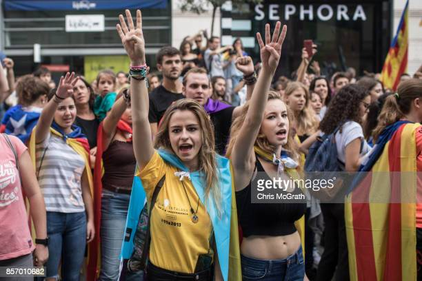 Peoiple chant slogans and sing songs as thousands of citizens gather in Plaza Universitat during a regional general strike to protest against the...