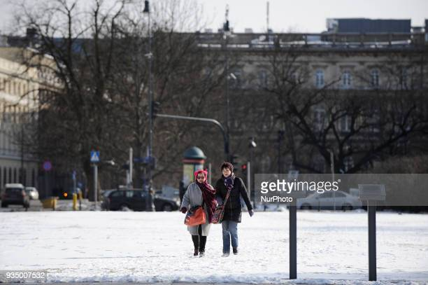 Peole are seen walking in the snow on Pisludski Square in Warsaw Poland on March 17 2018 A sudden drop in temperatures and sustained snow fall have...